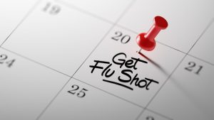 Concept image of a Calendar with a red push pin. Closeup shot of a thumbtack attached. The words Get Flu Shot written on a white notebook to remind you an important appointment.